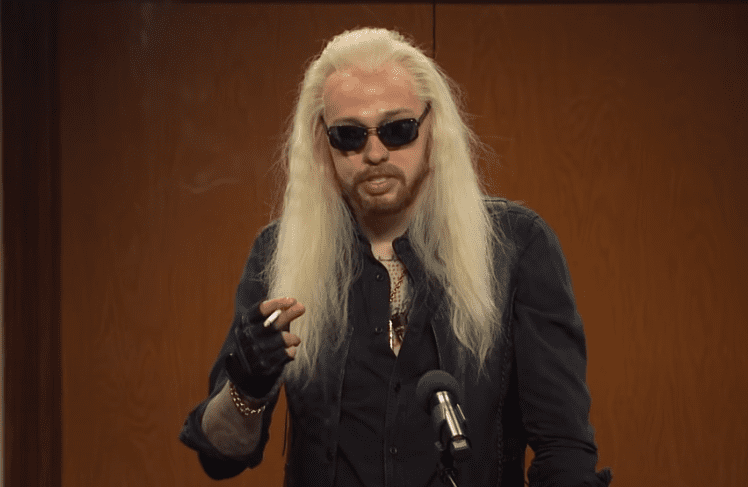 A person with long hair and a beard wearing sunglasses and a black jacket