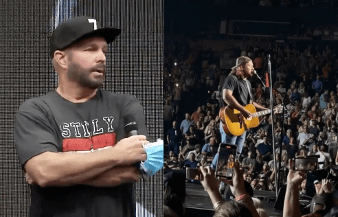 Garth Brooks holding a guitar and a microphone with a crowd watching