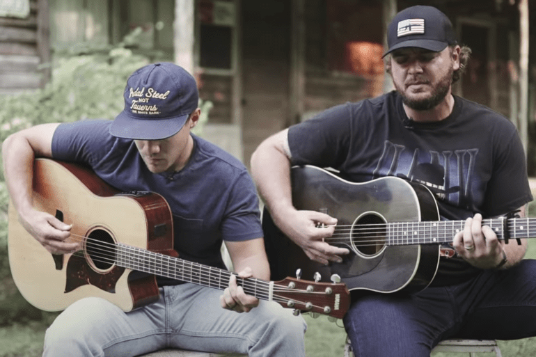A couple of men playing guitars