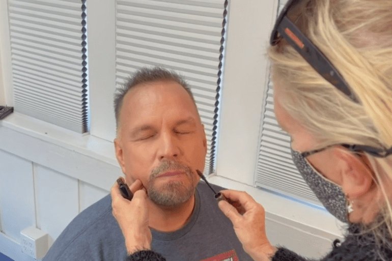 Garth Brooks with a beard talking on a cell phone
