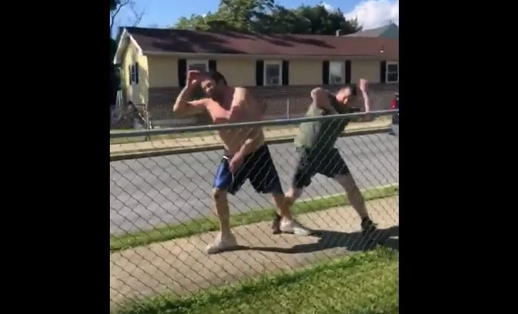 A person kicking another man
