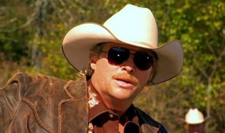 A person wearing a cowboy hat and sunglasses